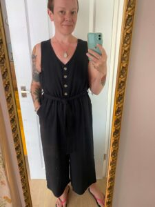 A woman wearing a black culottes playsuit, with v-neck, tie belt, and contrast buttons down the front.
