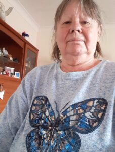 A woman wearing a grey long-sleeved top with a large blue sequined butterfly decorating the front.