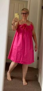 A woman wearing a sleeveless bright pink knee-length dress with a ruffle across the neckline.