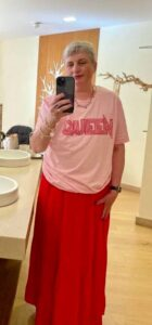 A woman wearing a floor length red skirt and a pink t-shirt with the word 'QUEEN' in red stitching across the chest.