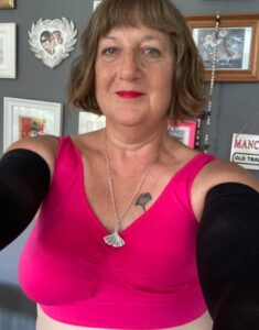A woman wearing a bright pink crop top. She has a right breast and is not wearing a prosthesis on her left side.