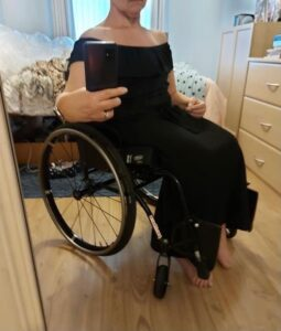 A woman wearing a full-length black dress, off-the-shoulder with a Bardot ruffle. The woman is sitting in a wheelchair.