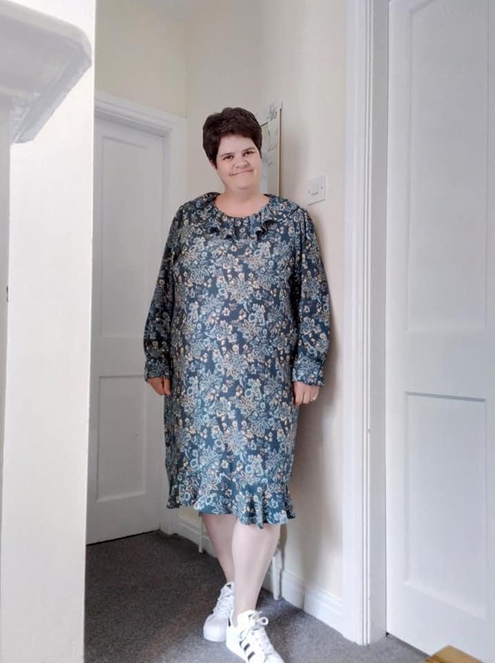 A woman wearing a knee length blue floral dress with frilled collar. It has gathered full length sleeves and a frilled hem.