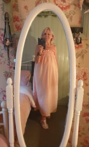 A woman wearing a long, loose-fitting, sleeveless pale pink dress with a gathered shirred neckline.